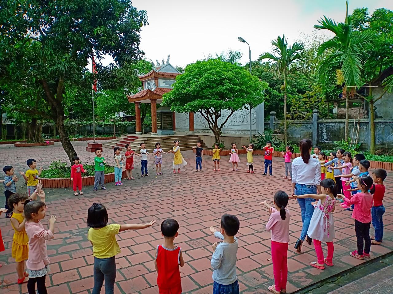 Cô và trẻ cùng chơi trò chơi trong sân khu tưởng niệm